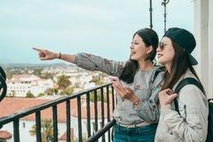 Schwestern, die etwas auf dem Balkon finden stockfotografie