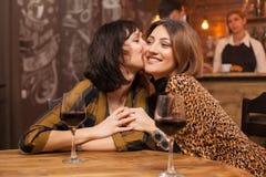 Schwestern, die ihre Freundschaft klatscht über einem Glas Wein in einer Weinlesekneipe feiern lizenzfreie stockfotos