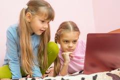 Schwestern, die Laptopkarikatur betrachten Stockfotografie