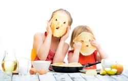 Schwestern, die Pfannkuchen kochen lizenzfreies stockbild