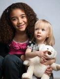 Schwestern, die Spielzeugbären lächeln und anhalten Stockfotos