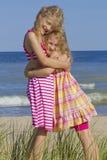 Schwestern, die am Strand umarmen. lizenzfreies stockfoto