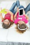 Schwestern, die Videos auf ihren Tablet-Computern aufpassen Stockfotos