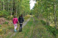 Schwestern, die in Wald gehen lizenzfreie stockfotografie