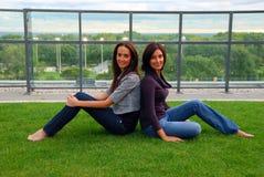 Schwestern, die zurück zu Rückseite sitzen lizenzfreies stockbild