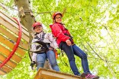Schwestern, die zusammen im Hochseilgarten klettern Stockbilder