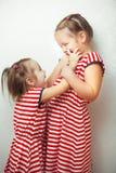 Schwestern mit Frisuren und selben kleidet Haben des Spaßes lizenzfreies stockfoto