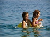 Schwestern mit Strandspielzeug (Ringe) Lizenzfreie Stockfotos