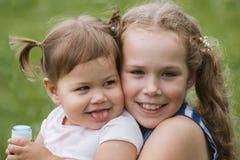 Schwestern mit zwei Babys, die im Park, Gehen im Freien spielen Stockfotografie