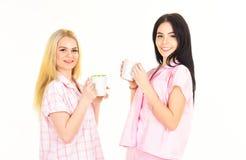 Schwestern oder beste Freunde in den Pyjamas Morgenkaffeekonzept Blond und Brunette auf lächelnden Gesichtern hält Becher mit Kaf Lizenzfreies Stockfoto
