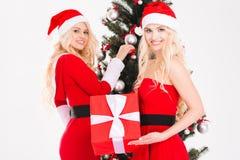 Schwestern paart das Halten anwesend und die Verzierung des Weihnachtsbaums Stockbild