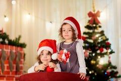 Schwestern paart Kind in den Weihnachtshüten Sankt mit Geschenken nahe Stockfotografie