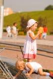 Schwestern spielen am Brunnen Stockbilder