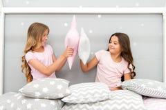 Schwestern spielen Kissenschlafzimmerpartei Kissenschlachtpyjamapartei Zeit zum Spaß glätten Sleepoverparteiideen Drei glückliche lizenzfreie stockfotos