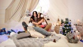 Schwestern umfassen sich mit guten Rutsch ins Neue Jahr, Freunde warten auf Weihnachten mit Geschenken und Weihnachtsbaum, jung stock video footage