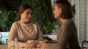 Schwestern, welche die angenehmen Nachrichten zusammen sich schauen, Zeit, Freundschaft besprechen stockbild