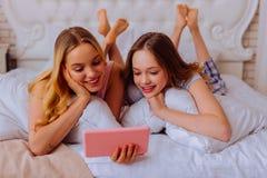 Schwestern, welche die Pyjamas kühlen im Bett tragen und Film aufpassen lizenzfreie stockfotos