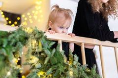 Schwesterstellung auf Treppenhaus mit Kleinkindmädchen und Warteweihnachtsgeschenken lizenzfreie stockfotos
