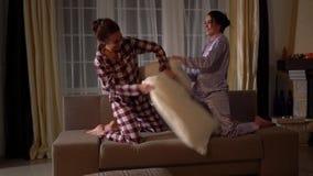 Schwesterzwillinge, die Spaß mit Lachen und Lächeln haben und mit Kissen am Abend in einem gemütlichen Wohnzimmer kämpfen stock footage