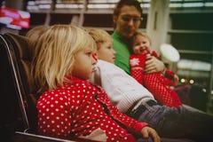 Schwierigkeiten in der Reise mit Kind-verärgerter unglücklicher Wartezeit des kleinen Mädchens im Flughafen mit Familie lizenzfreie stockfotos