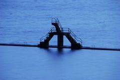 Schwimmbad, Sprungbrett und Meer Stockfotos
