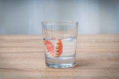 Schwimmen der falschen Zähne im transparenten Wasserglas Lizenzfreie Stockfotografie