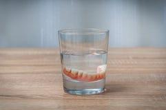 Schwimmen der falschen Zähne im transparenten Wasserglas Stockfotografie