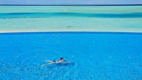 Schwimmen der jungen Frau über Unendlichkeitspool in den Tropen stock video footage