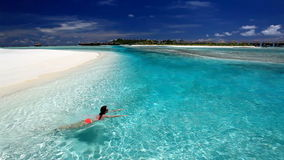 Schwimmen der jungen Frau in der tropischen Lagune