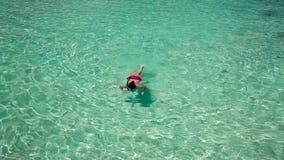Schwimmen der jungen Frau in einer korallenroten Lagune stock video footage