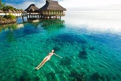Schwimmen der jungen Frau in einer korallenroten Lagune Stockfotos