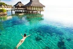 Schwimmen der jungen Frau in einer korallenroten Lagune Stockfotografie