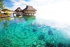 Schwimmen der jungen Frau in einer korallenroten Lagune stockfoto