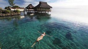 Schwimmen der jungen Frau in einer korallenroten Lagune stock video