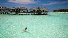 Schwimmen der jungen Frau in einer korallenroten Lagune stock footage