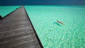 Schwimmen der jungen Frau in einer korallenroten Lagune nahe bei Anlegestelle stock video