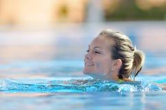 Schwimmen der jungen Frau im Pool Stockfotos