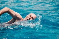 Schwimmen des älteren Mannes auf dem blauen Ozean - Gesundheits- und Tätigkeitskonzept lizenzfreies stockfoto