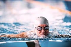Schwimmen des älteren Mannes in einem Innenswimmingpool Stockfotografie