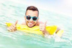 Schwimmen des jungen Mannes auf matress Stockfoto