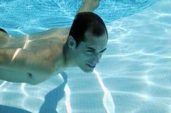 Schwimmen des jungen Mannes im Pool lizenzfreies stockbild