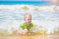 Schwimmen des kleinen Jungen im Meer, im Betrieb und im Spritzen in den Wellen von reinem lizenzfreie stockbilder