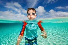 Schwimmen des kleinen Jungen im Ozean Lizenzfreies Stockfoto