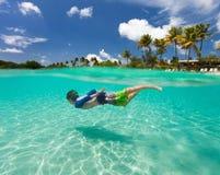 Schwimmen des kleinen Jungen im Ozean Lizenzfreie Stockbilder