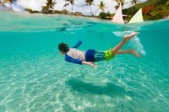 Schwimmen des kleinen Jungen im Ozean Lizenzfreies Stockbild