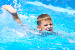 Schwimmen des kleinen Jungen im Pool Lizenzfreie Stockbilder