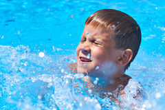 Schwimmen des kleinen Jungen im Pool Stockbilder