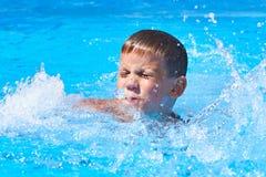 Schwimmen des kleinen Jungen im Pool Lizenzfreies Stockfoto