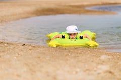 Schwimmen des kleinen Jungen in Meer mit Gummiring Stockbild