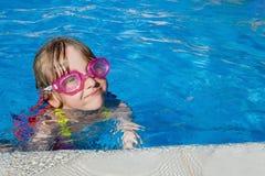 Mädchenschwimmen im Pool mit Schutzbrillen Stockbilder